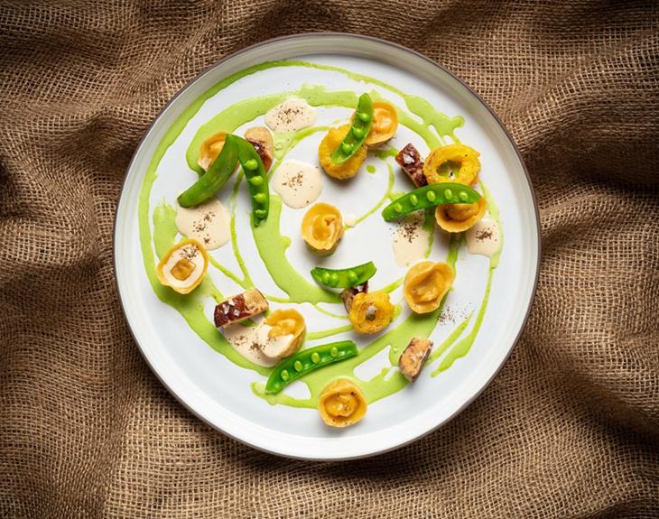 Foie gras ravioli, spinach, onions, green peas